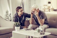 镇定下来变老的银发被毁坏的父亲的年轻深色头发的宜人的儿子 免版税库存图片