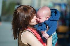 镇定她哭泣的婴孩的年轻母亲 免版税图库摄影