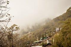 镇意想不到的秀丽喜马拉雅山山,剧烈的峭壁surrond小山倾斜的镇在一个有雾的冬日 _ 图库摄影