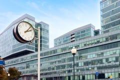 镇时钟企业在蓝领的大厦背景 免版税库存图片