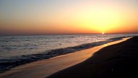 镇静令人满意减慢碰撞在沙子海滩在壮观的温暖的晚上橙色日落海景的海岸海岸线的波浪 股票录像