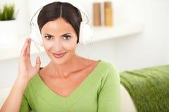 镇静地听到音乐的可爱的妇女 免版税库存照片