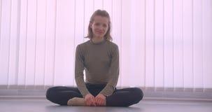 镇静地坐在莲花姿势的白种人专业芭蕾舞女演员特写镜头画象在轻的演播室微笑的地板入 股票视频