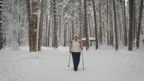 镇静妇女向体育求助在她在运动服温暖地穿戴的冬天冷的森林里 是精力充沛地沿Th 影视素材