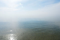 镇静平静的蓝色海没有波浪和有有雾的backgroudn的 库存照片