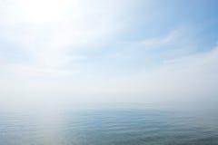 镇静平静的蓝色海没有波浪和有有雾的backgroudn的 免版税库存图片