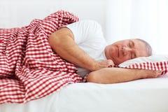 镇静成熟人在床上睡觉 图库摄影