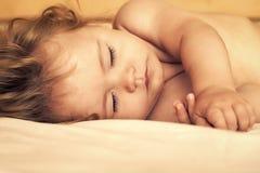 镇静睡觉的孩子 睡觉的婴孩在床上 图库摄影