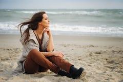 镇静美丽的妇女单独坐海滩沙子并且看水 库存照片