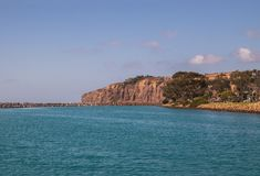 镇静蓝绿色水美好的大身体与一只非常长的岩石跳船在边和大峭壁的在背景中 库存照片