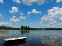 镇静蓝色湖和小船有松的白色云彩的 免版税库存照片