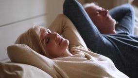 镇静资深中部变老了夫妇放松的倾斜在舒适的长沙发 股票视频