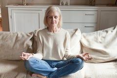 镇静资深思考在长沙发的女子实践的瑜伽 库存照片