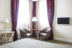镇静颜色、就座区域、扶手椅子和窗口的旅馆客房 库存图片