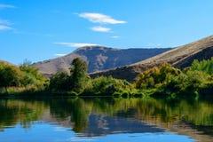 镇静水,豪华的绿色岸由软的绵延山滴下了 库存图片