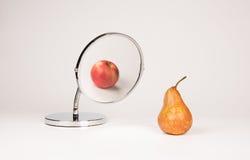 镜子反射的苹果和梨 免版税库存图片