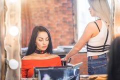 镜子的美丽的深色的妇女在化妆师的一个招待会,美发师 库存照片