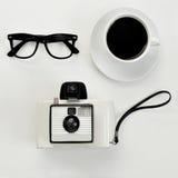 镜片、咖啡和快速照相机 免版税库存图片
