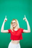镜片、红顶和白色裙子的逗人喜爱的金发碧眼的女人由两个手指出现  演播室短绿色的美丽的女孩 库存照片