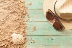 镜片和帽子在木背景与沙子 库存图片