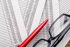 镜片和红色笔在文件顶部 库存图片