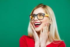 镜片和红顶的笑的女孩在绿色背景 年轻金发碧眼的女人特写镜头画象有长的头发的和 免版税库存图片