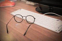 镜片和键盘在木桌上晚上,关闭 图库摄影