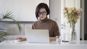 镜片的亚裔妇女与膝上型计算机一起使用在白色家庭办公室