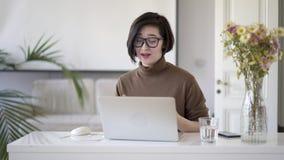 镜片的亚裔妇女有视频聊天在膝上型计算机在家庭办公室 股票录像