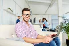 镜片的人有运转在办公室的膝上型计算机的 免版税图库摄影