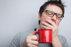 镜片的困打呵欠的人有红色茶的或咖啡有蓬乱的头发在轻的背景,早晨的内衣刷新 库存图片
