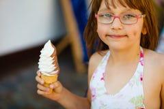 镜片的小孩女孩吃冰淇凌的 库存照片