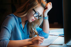 镜片的工作白肤金发的白种人的女实业家写某事与铅笔和直到很晚 库存图片