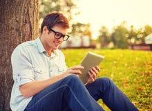 镜片的微笑的男学生有片剂个人计算机的 免版税库存照片