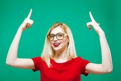 镜片的微笑的金发碧眼的女人由两个手指出现  演播室短绿色背景的美丽的女孩 图库摄影