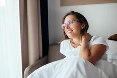 镜片的愉快的微笑的妇女在卧室见面新的天 图库摄影