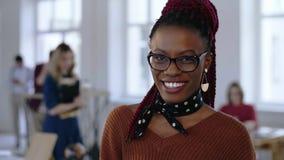 镜片的有白色牙的微笑在办公室的年轻非洲创造性的女商人令人惊讶的特写镜头画象  股票录像