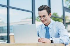 镜片的英俊的微笑的年轻人使用膝上型计算机外面 库存图片