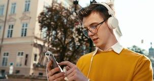 镜片的英俊的白肤金发的少年是enj oying的音乐通过耳机和浏览,聊天和发短信在 影视素材