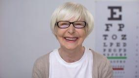 镜片的资深女性微笑对照相机的,满意对服务质量 影视素材