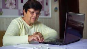 镜片的资深老妇人在家检查每日费用的费用在膝上型计算机的 股票视频