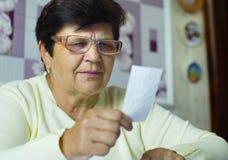 镜片的资深老妇人在家检查每日费用的费用 图库摄影