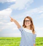 镜片的逗人喜爱的小女孩指向在天空中的 库存照片