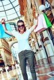 镜片的高兴愉快的时尚的妇女有购物袋的 库存照片