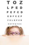 镜片的滑稽的女孩有视力检查表的 免版税库存图片