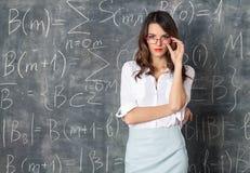 镜片的年轻聪明的俏丽的妇女临近黑板 免版税库存图片