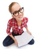 镜片阅读书的微笑的十几岁的女孩 免版税库存照片
