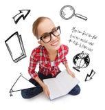 镜片阅读书的微笑的十几岁的女孩 免版税图库摄影