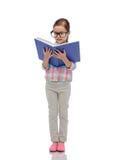镜片阅读书的愉快的小女孩 免版税图库摄影