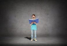 镜片阅读书的愉快的小女孩 免版税库存照片